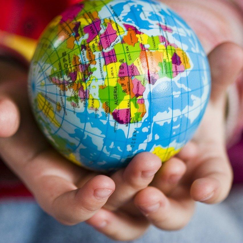 Lapsi pitää käsissään maapalloa esittävää palloa.