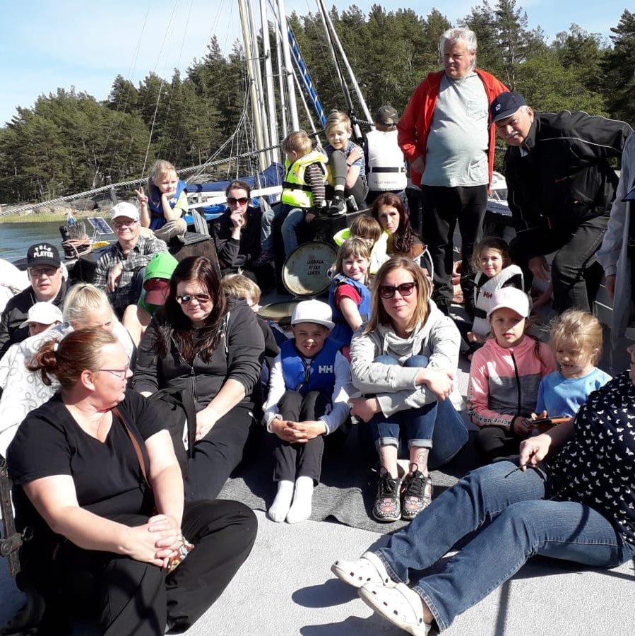 Ihmisiä seisomassa ja istumassa laivan peräosassa.