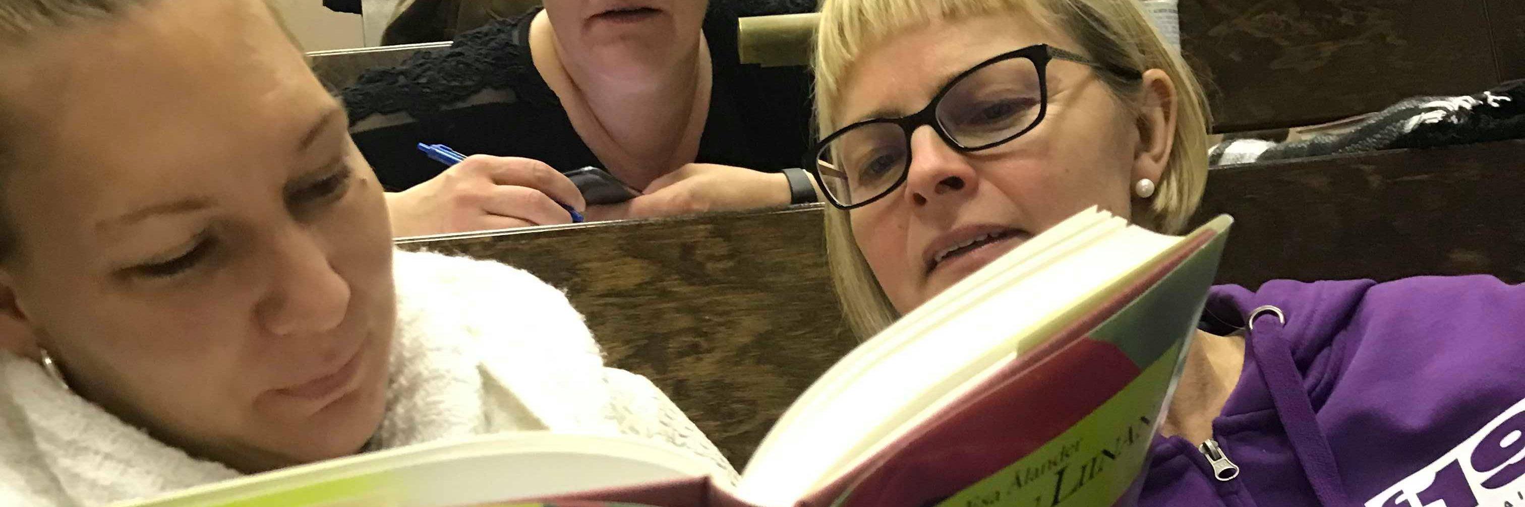 Kaksi henkilöä lukemassa Punaisen liinan lapset -kirjaa.